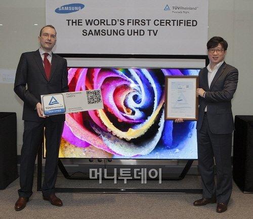 ↑4일 삼성전자 수원 디지털시티에서 삼성전자 영상디스플레이사업부 유준영 상무(사진 오른쪽)가 'TUV 라인란드' 한국 지사장 카스텐 리네만(Carsten Lienemann)으로부터 UHD TV 인증서를 전달 받고 있다.
