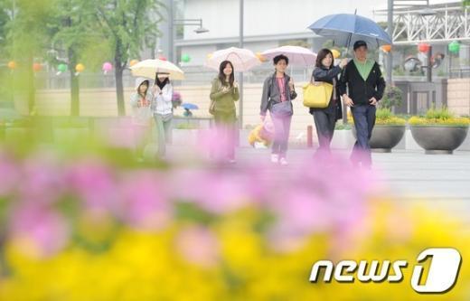 서울 광화문광장에서 시민들이 우산을 쓴 채 발걸음을 재촉하고 있다.  News1 허경 기자