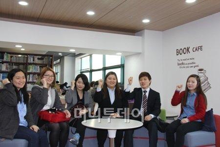 2013 글로벌현장실습 참가자들이 대학 도서관 북카페에서 파이팅을 외치며 서로를 격려하고 있다<br />