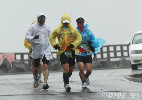 ↑ 2013 제주국제울트라 마라톤 참가자들이 비바람을 뚫고 역주하고 있다. [사진제공=양성규 씨]