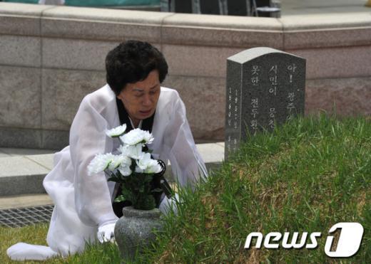 5·18민중항쟁 제33주년 추모제가 열린 17일 오전 광주 북구 운정동 국립 5·18민주묘지에서 한 유가족이 희생자의 묘소를 찾아 눈물 흘리고 있다. 2013.5.17/뉴스1  News1   정회성