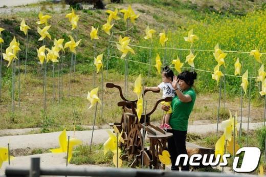 故 노무현 전 대통령 4주기를 하루 앞둔 22일 오후 김해 봉하마을에 설치된 노란 바람개비 앞에서 시민들이 사진을 찍고 있다. 2013.5.22/뉴스1  News1 전혜원 기자