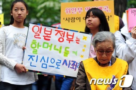 지난달 29일 서울 종로구 중학동 주한 일본대사관 앞에서 열린 제 1076차 일본군 위안부 문제해결을 위한 정기 수요시위에 참석한 김복동 할머니 뒤에  선 어린이들이 손팻말을 들고 있다.  News1 한재호 기자