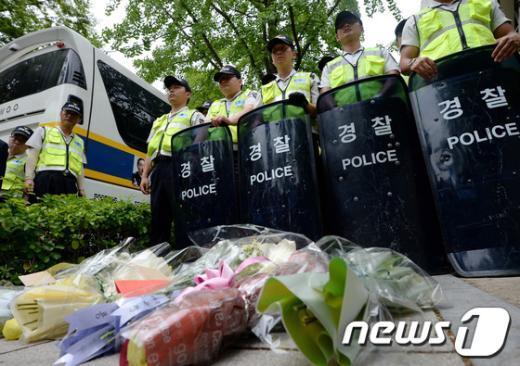 [사진]기자들 취재 막은 경찰, 바닥에는 꽃다발과 성명서만