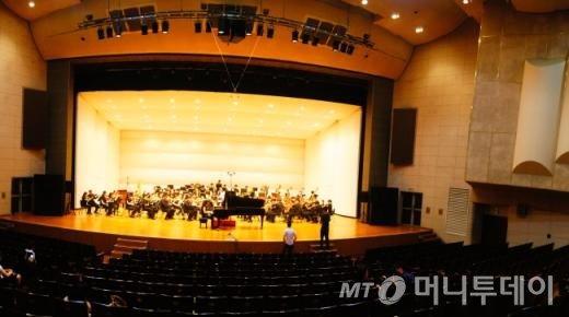피아니스트와 리허설 중. 관객석엔 오케스트라 단원들의 가족들과 스텝들이 드문드문 앉아있다.