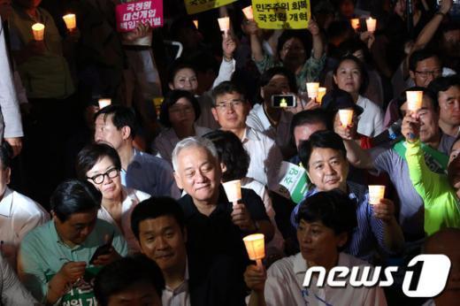 """3일 오후 서울 청계광장에서 열린 """"국가정보원 대선 개입"""" 의혹에 대한 국정조사 기간 연장을 촉구하는 제5차 국민촛불대회에 참석한 민주당 김한길 대표를 비롯한 의원들이 촛불을 들고 구호를 외치고 있다. 장외 투쟁 사흘째를 맞은 김 대표를 비롯한 의원들은 이날 같은 장소에서 """"민주주의 회복 및 국정원 개혁촉구 국민보고대회""""를 열고 시민단체 촛불집회에 합류했다. 2013.8.3/뉴스1  News1   한재호 기자"""