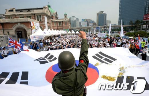 한국자유총연맹 회원들이 서울역 광장에서 열린 나라사랑 공감한마당 행사에서 대형태극기를 펼치고 만세삼창을 하고 있다.  News1 박정호 기자