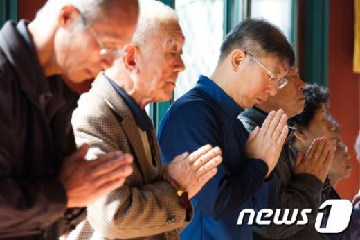 대입 수학능력시험을 앞두고 서울 종로구 조계사 대웅전을 찾은 수험생 자녀를 둔 학부모들이 정성스레 기도를 드리고 있다.   News1   유승관 기자