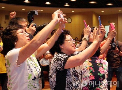 SK대학생 봉사단인 '써니'는 전국 노인종합복지관을 돌며 노인들을 상대로 문자 보내기, 사진 전송하기 등 휴대폰 사용법을 1대 1로 알려주고 있다. 사진촬영 연습을 하고 있는 모습/SK텔레콤 제공