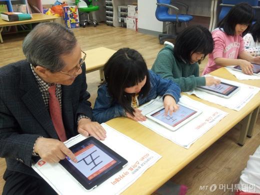 <br /> KT는 2010년 3월부터 누구나 쉽게 스마트기기를 사용할 수 있도록 '올레 스마트 아카데미'를 운영하고 있다. 할아버지와 아이들이 태블릿PC에 한자를 적고 있다./KT 제공 <br />