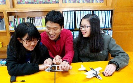 박영철 삼성전자 메모리사업부 EDS팀 과장(가운데)이 학생들에게 콘덴서 모형 비행기의 원리를 설명하고 있다. /사진=정지은 기자