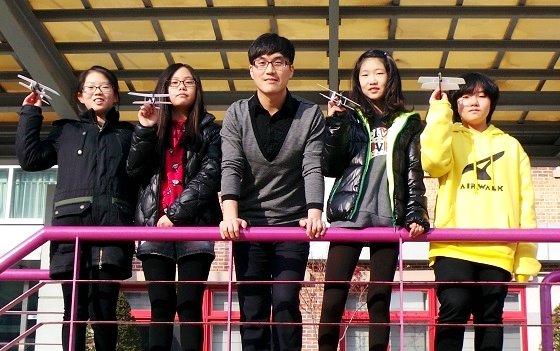 박종선 삼성전자 메모리사업부 EDS팀 사원(가운데)이 푸른초 6학년 학생들과 함께 운동장에서 콘덴서 모형 비행기를 날리며 활짝 웃고 있다. /사진=정지은 기자