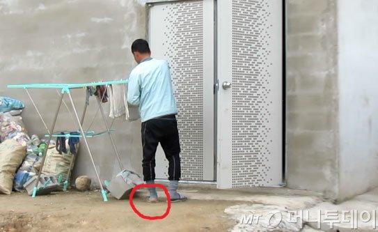 지난 1월24일 염전 노예로 끌려가 노역에 동원된 김모씨(40)의 모습. 한겨울에도 낡은 양말이 구멍 나 있다. 뒤편의 건물은 생활을 하던 자재창고. /사진=서울 구로경찰서
