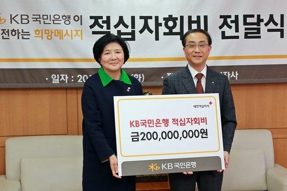 정윤식 국민은행 전략본부장(오른쪽)이 18일 서울 중구 대한적십자사 본사를 방문해 유중근 대한적십자사 총재에게2014년도 적십자회비로 2억원을 전달했다.(대한적십자사 제공)© News1