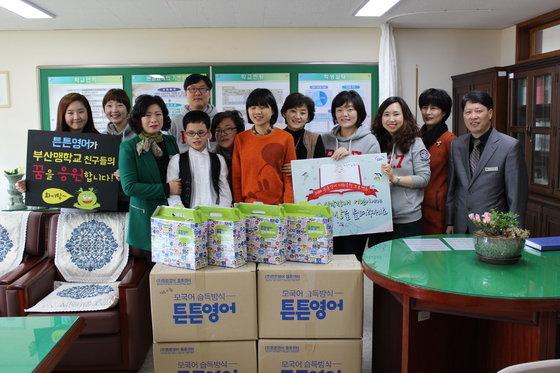 튼튼영어 임직원들이  부산맹학교 어린이들에게 점자로 된 영어 교재를  전달하고 있다. /  © News1