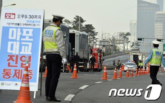 영화 어벤져스2 한국촬영이 시작된 30일 오전 서울 마포구 마포대교 진입로 앞으로 경찰들이 교통을 통제하고 있다. 서울지방경찰청은 이날 촬영으로 오후 5시30분까지 마포대교 1.6km 양방향이 통제돼 보행자와 차량은 서강대교와 원효대료로 돌아가한다고 밝혔다.2014.3.30/뉴스1 © News1   최영호 기자