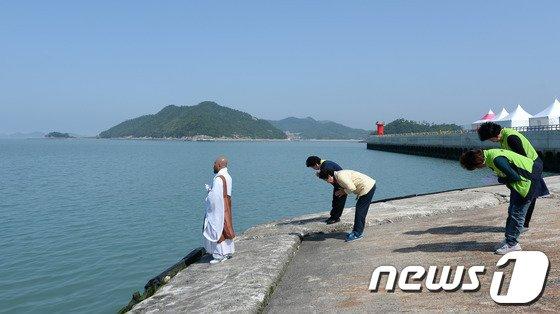세월호 침몰 사고 33일째인 18일 오전 전남 진도군 팽목항에서 스님과 진도읍 주민들이 사고해역을 향해 기도하고 있다. 2014.5.18/뉴스1 © News1   박지혜 기자