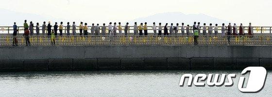 세월호 침몰 사고 33일째인 18일 오후 진도군 팽목항에서 스님들과 불자들이 실종자들의 무사귀환을 염원하며 방파제를 걷고 있다. 2014.5.18/뉴스1 © News1   박지혜 기자