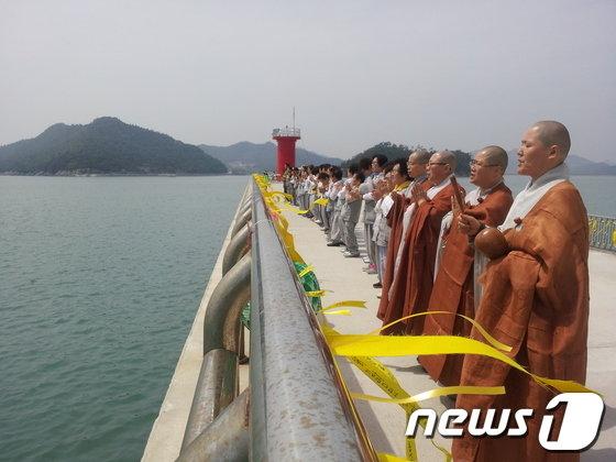 18일 오후 대한불교조계종 팽목항 법당에 기도를 위해 방문한 부산 마하선원 대중 스님과 신도들이 전남 진도군 팽목항 방파제에서 바다에 실종자의 귀환을 빌고 있다. © News1   문창석 기자