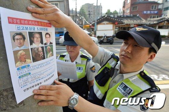 경찰관들이 22일 서울 종로구에서 유병언 전 세모그룹 회장의 수배전단지를 붙이고 있다. © News1 송은석 기자