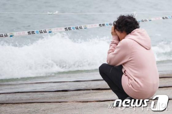 전남 진도 팽목항 앞바다에서 세월호 실종자 가족이 바다를 마주한 채 오열하고 있다.