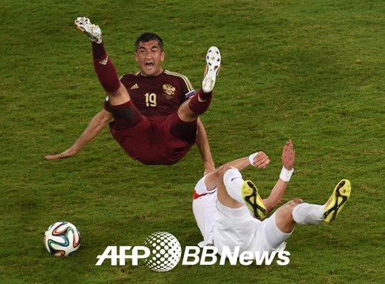 기성용이 사메도프(왼쪽)에게 거친 태클을 시도하고 있다. /사진=AFPBBNews<br /> <br />