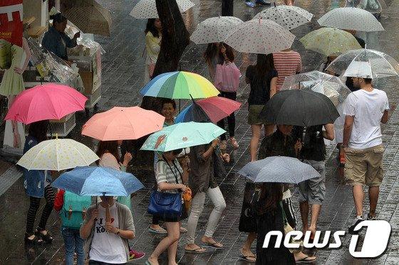 소나기가 내린 23일 오후 서울 중구 명동거리에서 시민들이 우산을 쓴 채 걸어가고 있다./뉴스1 © News1 민경석 기자