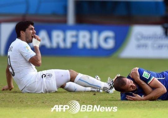 이탈리아 수비수 조르조 키엘리니(유벤투스)의 어깨를 문 뒤 자신의 이를 만지고 있는 우루과이 수비수 루이스 수아레스(리버풀)/ AFPBBnews=News1