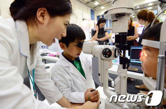[사진]흰 가운 입고 안과의사가 된 어린이
