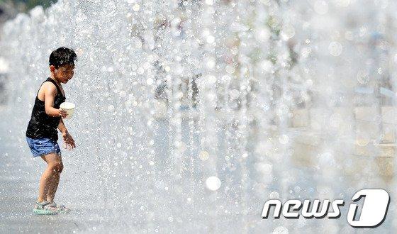 본격적인 더위가 시작된다는 절기상 소서인 7일 오후 서울 광화문 광장 분수를 찾은 어린이가 더위를 식히고 있다.2014.7.7/뉴스1 © News1   손형주 기자
