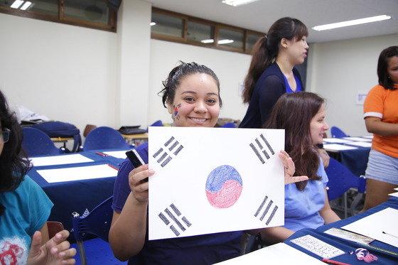 14일 숙명여대에서 열린 태극기 그리기 체험행사에 참여한 외국인 학생이 자신이 직접 그린 태극기를 들어보이며 웃고 있다. (숙명여대 제공) © News1