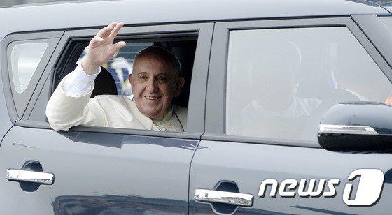 4박 5일 일정으로 한국을 방문한 프란치스코 교황이 14일 오전 서울공항에서 광화문을 거쳐 주한 교황 대사관으로 향하는 중 기아차 쏘울에 탑승해 시민들을 향해 손을 흔들고 있다. 프란치스코 교황은 취임 초기부터 방탄차를 이용하지 않겠다고 공언했으며, 실제 이번 한국 방문 때도 가장 작은 차를 타고 싶다는 뜻을 한국 천주교 교황방한준비위원회에 전달해온 것으로 알려졌다. 이에 따라 방한 기간 중 교황은 기아자동차의 1600cc급 소형 승용차인 쏘울을 탄다.2014.8.14/뉴스1 © News1 안은나 기자