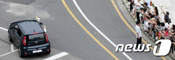 아시아 국가 중 처음으로 한국을 방문한 프란치스코 교황이 14일 포프모빌(POPE mobile, 교황 의전차량)로 낙점된 기아자동차 '쏘울'을 타고 서울 경복궁 앞을 지나며 환영 인파들에게 손인사를 하고 있다. 프란치스코 교황은 4박5일의 방한 기간 동안 아시아 가톨릭청년대회와 천주교 순교자 124위 시복식 등 4차례 미사를 집전하고 세월호 참사 생존자와 희생자 가족, 일본군 위안부 피해자 등을 만날 예정이다. 2014.8.14/뉴스1 © News1 오대일 기자