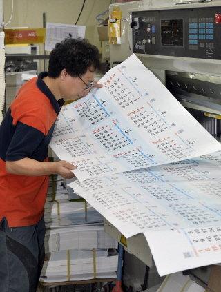 (서울=뉴스1) 최영호 기자 = 서울 충무로 한 인쇄소에서 직원이 인쇄된 2014년 새해 달력을 살펴보고 있다. 2014년은 대체 휴일제 시행으로 공휴일이 2002년 이후 12년 만에 가장 많은 67일로 표기 돼 있다.