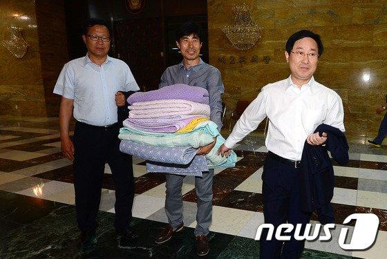 [사진]침구류 들고 예결위회의장 나서는 새정치연합 의원들