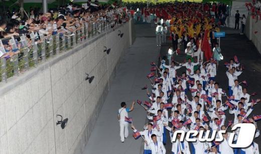 [사진]손 흔들며 경기장 들어서는 북한 선수단