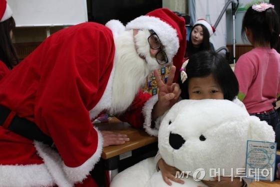 부스러기사랑나눔회와 LG디스플레이가 연 '크리스마스의 기적' 중 모 지역아동센터의 아동이 그동안 받고 싶어하던 곰인형을  '산타'로부터 선물 받고 있다./사진=부스러기사랑나눔회