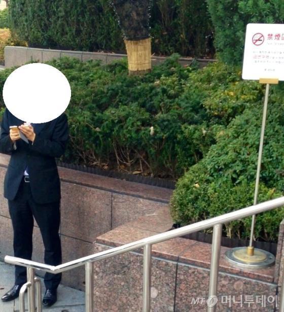 금연 표지판 앞에서 담배를 피우는 중국인.
