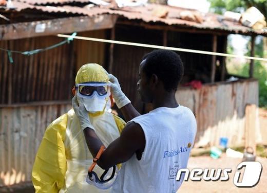 12일(현지시간) 한 시에라리온 적십자 대원이 에볼라 감염 사망자 시신 이송작업을 앞둔 동료 대원의 보호장비를 점검해주고 있다.© AFP=뉴스1 2014.11.13/뉴스1 © News1