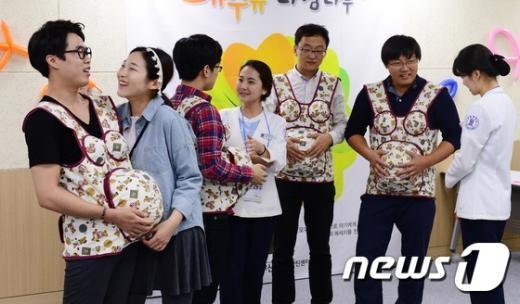 임산부의 날을 앞두고 산모건강증진센터에서 임산부들의 남편들이 약 10kg의 임신체험복을 착용하는 '남편임신체험'을 하고 있다. © News1 박지혜 기자