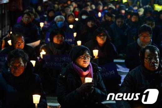 """통합진보당 정당 해산심판 선고일을 하루 앞둔 18일 오후 서울 종로구 계동 현대건설 본사 맞은편에서 열린 """"정당해산 반대 민주수호 촛불문화제""""에 이정희 통합진보당 대표를 비롯한 통진당원들이 촛불을 든채 참석하고 있다. 2014.12.18/뉴스1 © News1 민경석 기자"""
