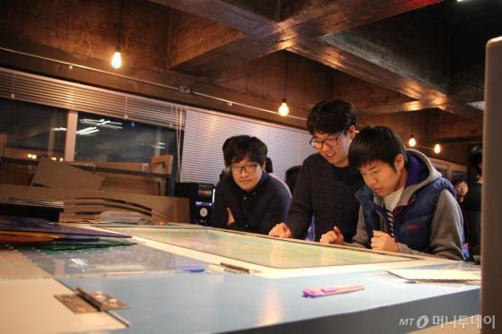 팹랩 서울에서 레이저 커터를 이용해 아이디어를 상품으로 직접 만들어보고 있는 청년들