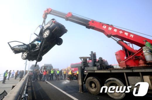 인천 영종대교 70중 추돌사고로 1명이 사망하고 30여명의 부상자가 발생한 11일 사고 현장 에서 견인할 수 없는 차량을 도로 밖으로 옮기고 있다. 인천 영종대교 70중 추돌사고는 영종대교 상부도로 인천국제공항 방면에서 서울 방향으로 달리던 차량들이 잇따라 추돌하면서 일어난 것으로 알려졌다. 사고는 가시거리 50m 미만의 짙은 안개 속에서 발생한 것으로 알려졌다. 최초 4중 추돌로 시작된 사고는 시간이 지나면서 사고 차량을 미처 보지 못한 후속 차량의 추돌로 70중 대형사고로 이어졌다. 2015.2.11/뉴스1 © News1 박정호 기자