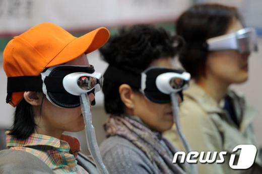 안구건조증 치료기기를 체험하고 있는 시민들./© News1