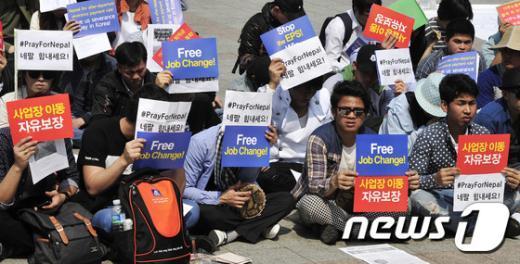 26일 오후 서울 종로구 보신각 앞에서 열린 '2015 이주노동자 노동절집회'에서 참석자들이 '네팔 힘내세요'라고 적힌 손팻말을 들고 있다.2015.4.26/뉴스1 © News1