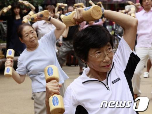 나무 아령을 들고 체조를 하고 있는 일본 노인들./© AFP=News1