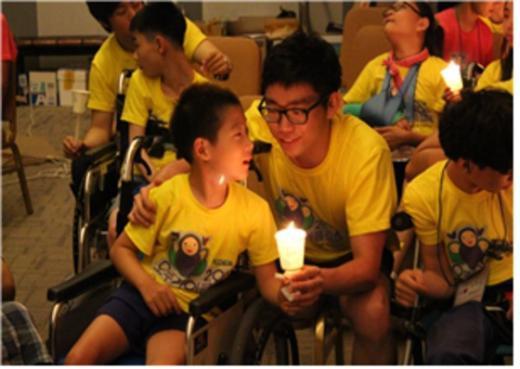 지난해 열린 오뚜기 여름캠프에 참가한 학생이 자원봉사자와 촛불을 맞잡고 있다. (한국뇌성마비복지회 제공) © News1