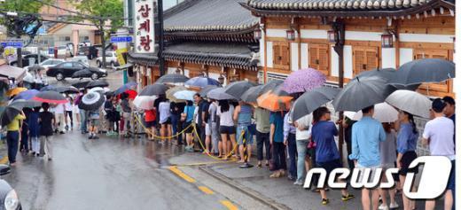 지난 12일 많은 시민들이 서울 종로구 한 삼계탕 식당앞에서 우산을 쓴 채 줄지어 서 있다./뉴스 © News1 김명섭 기자