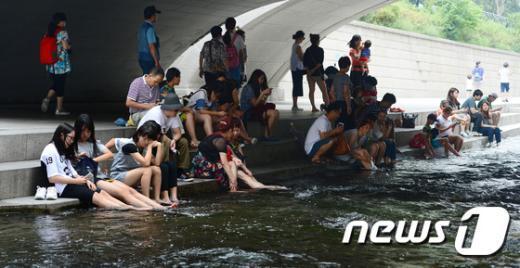 서울 지역 낮 최고기온이 36도까지 오른 30일 오후 서울 종로구 청계천에서 시민들리 물에 발을 물에 담그며 더위를 식히고 있다. 2015.7.30/뉴스1 © News1 민경석 기자