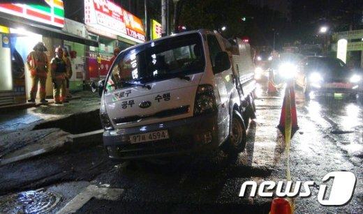 [사진]침하된 도로에 빠진 구청 청소차량